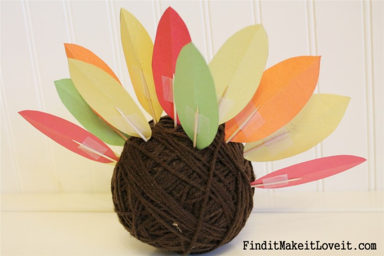 Toothpicks attached to paper feathers for a cute yarn ball turkey